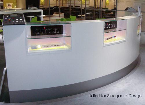 Buet vægparti med 4 indbyggede glasmontre med lys, væggen udført i sprøjtelakeret MDF.