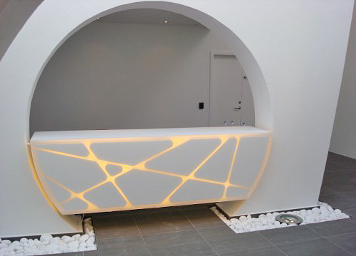 Receptionsskranke udført i hvidlakeret MDF, beklædt med opalhvid acryl og monteret med lys.
