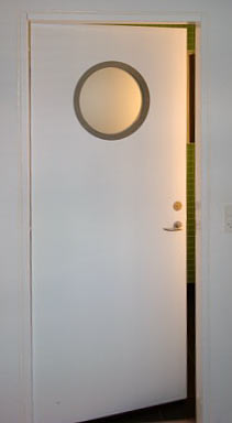 """Dørparti til toilet/bad med """"ko-øje"""" i rustfrit stål, monteret med satineret glas."""