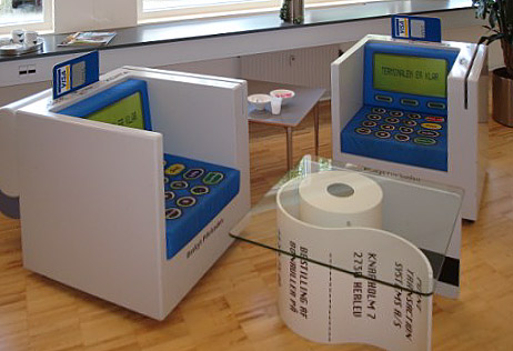 Stole udført som betalingsautomater, hynder med printet dekoration, den ene stol med printer på bagsiden. Bord udført som printerrulle og betalingskort, bordplade i glas.
