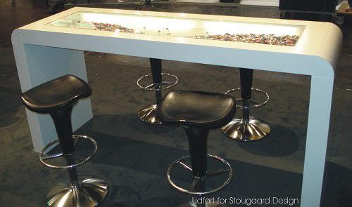 Udstillingsbord med nedbygget dekorationsplads med glas og lys.